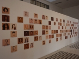 A thoughtful art installation with pictures of people shown as pantone samples of their skin colour