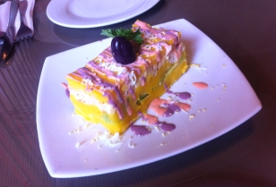 A more traditional version of a causa, this one filled with avocado and crab. The purple dressing is olive flavoured.
